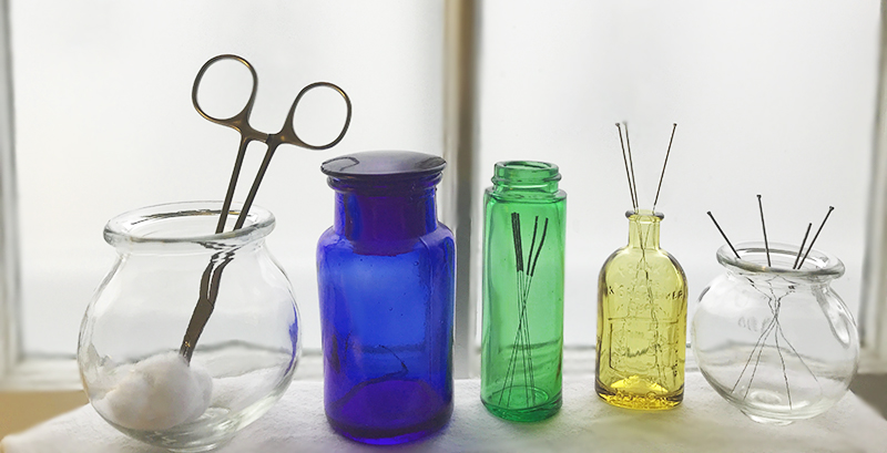 Picture of needles in colored jars against a frosted glass window backdrop